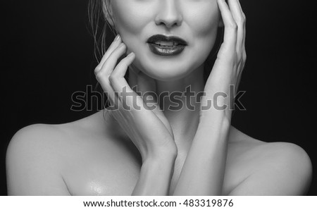 Close up lips and hands of young caucasian smiling and surprised blonde woman with red lips on black background. Black and white