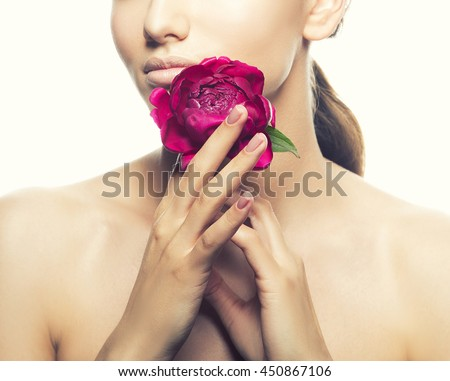 Close-up lips and shoulders of caucasian young brunette woman with peony flower in hand. Studio portrait. Isolated on white background. Toned.