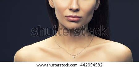 Close-up lips and shoulders of young brunette caucasian attractive sad woman with natural make-up. Studio portrait. Toned - stock photo