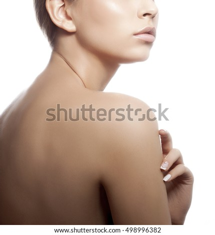 Close-up lips, back and shoulders of young caucasian girl with natural make-up, perfect skin and green eyes touch her skin isolated on white background. Studio portrait.