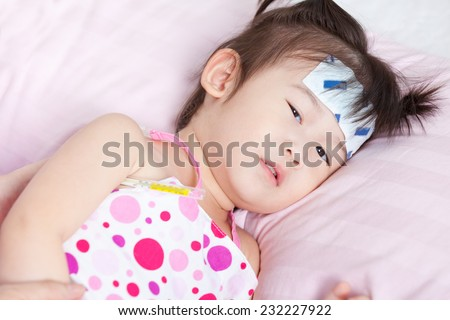 Close-up little asian girl lying  on sickbed with mercury thermometer in her armpit and cooling fever patch on her forehead - stock photo