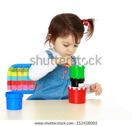close-up little girl playing while sitting at the table.Isolated on white. - stock photo