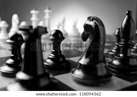 Close up low angle corner view of chess pieces lined up on a chess board ready for a game with focus to a black pawn with a castle and knight in the foreground