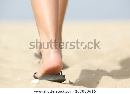 Close up low angle feet walking in flip flops on beach - stock photo