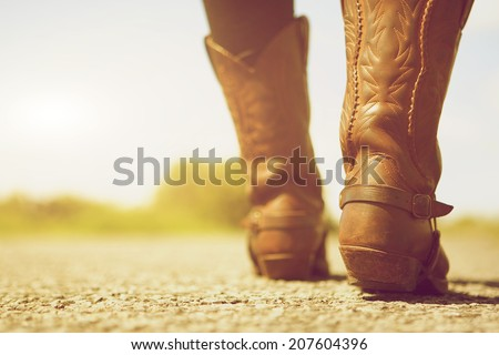 Close up low angle female with cowboy boots - stock photo