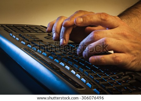 Close up low angle view of a man typing on a laptop computer in darkness conceptual - stock photo
