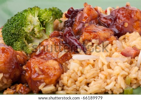 Close up macro detail of General Tso's chicken with broccoli and pork fried rice. Shallow depth of field. - stock photo