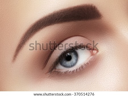 Close-up macro of beautiful female eye with perfect shape eyebrows. Clean skin, fashion naturel make-up. Good vision  - stock photo