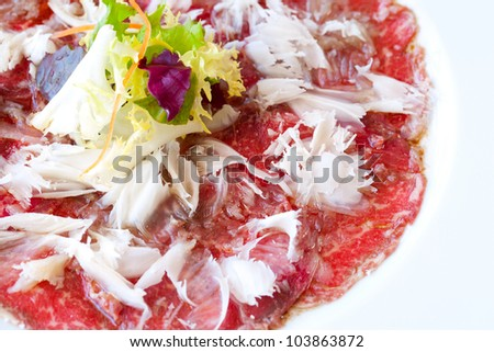 Close up macro of beef carpaccio with parmesan cheese flocks. - stock photo