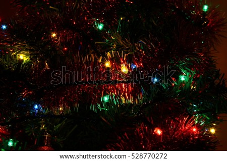 Close up macro shot of Christmas tree color lights with globes and decorations