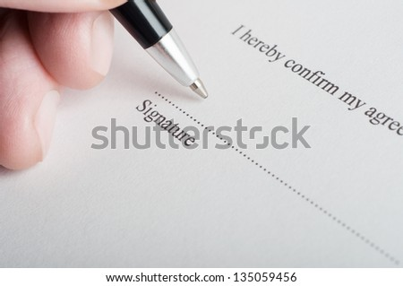 Close up (macro) shot showing fingers of a male hand, holding a pen, poised to sign on the dotted line of a legal document or contract. - stock photo