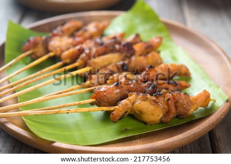Close up Malaysian chicken satay on wooden dining table, one of famous local dishes. - stock photo