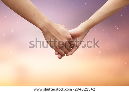 close up male and female hands holding together on blurred twilight sky backgrounds. passion in love concept. - stock photo