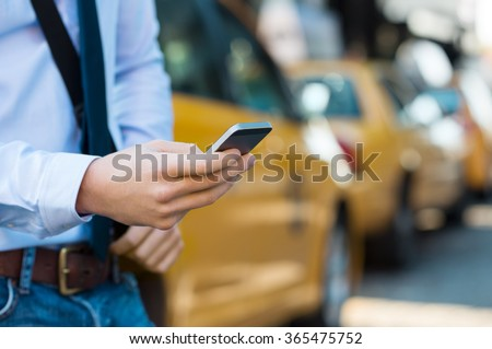 Close up male hand calling a taxi with a smartphone app. Close up of a businessman using mobile phone. Closeup detail of a businessmanâ??s hand holding a cellphone with yellow taxi in background.  - stock photo