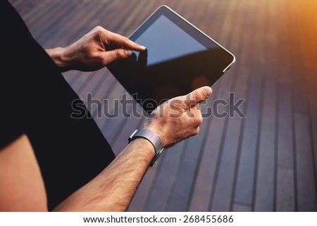Close up male student hands using touch pad against wooden background, freelancer man working on his digital tablet with big copy space, hipster man's hands browsing with touchscreen device, flare - stock photo