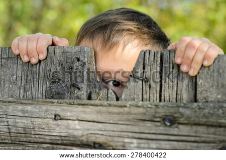 Close up Male Young Kid Peeking Over a Rustic Wooden Fence While Holding the Edge and Staring at the Camera - stock photo