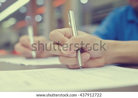 close up man hand with pen sign signature on paper application:student doing examination in the class:education and business.man writing letter on paperwork report:estimating quality annual concept - stock photo
