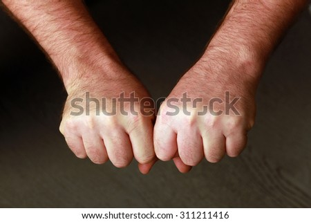 close-up man's fist on a gray background studio