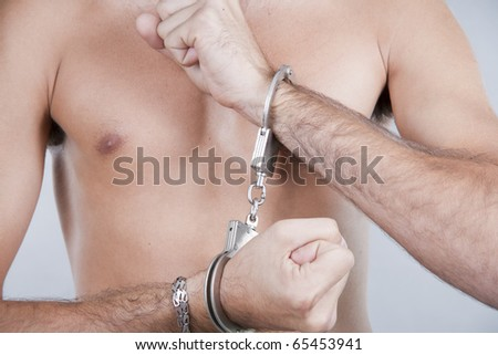 close-up man's hands chained in handcuffs - stock photo