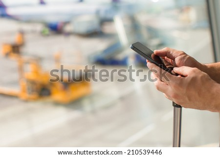 Close up man's hands using mobile phone inside airport - stock photo