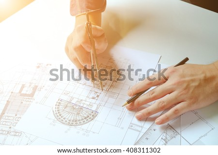 Close up man working of Architect sketching a construction project on his plane project at site construction work - stock photo