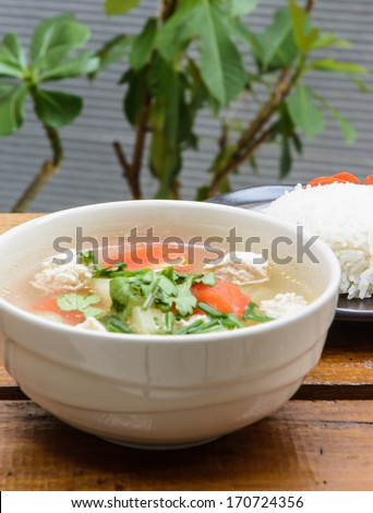 close up meat and vegetable soup in bowl and rice on dish at wood table