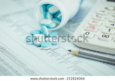 Close up Medicine pills and calculator on paper sheet - stock photo