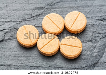 Close up medicine tablets on black color stone, medical and health care concept - stock photo