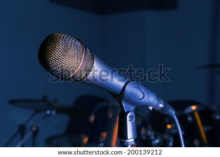 close-up Microphone on stage with drums and light blue dark background  - stock photo