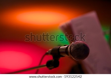 Close up microphone on stage with notebook and colored lights in the background.