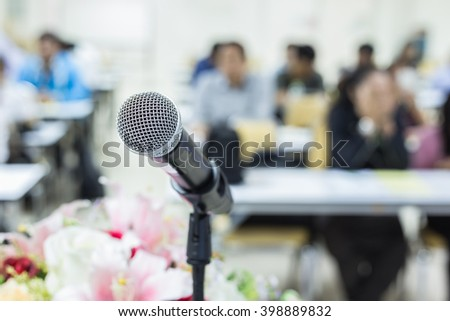 Close up microphone on the desk in meeting room with blur people background