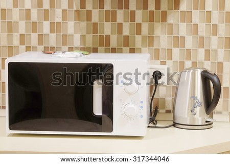 Close-up microwave and stainless electric kettle - stock photo
