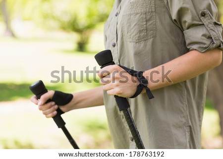 Close-up mid section of a beautiful young woman Nordic walking in the park - stock photo