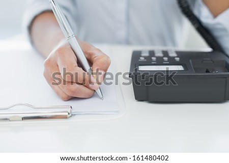 Close up mid section of a businesswoman using telephone while writing on clipboard at desk - stock photo
