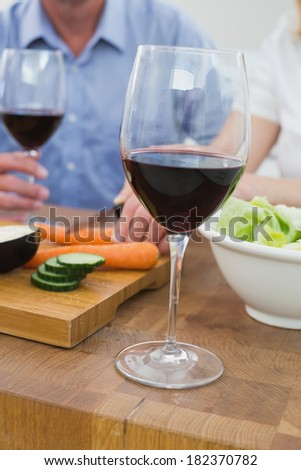 Close-up mid section of a couple with wine glasses and vegetables in the kitchen at home