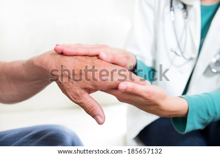 Close-up mid section of a doctor holding patients hands - stock photo
