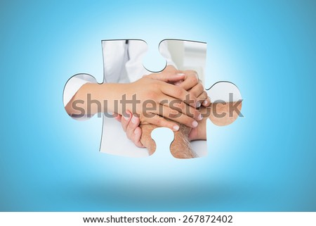 Close-up mid section of a doctor holding patients hands against blue background with vignette - stock photo