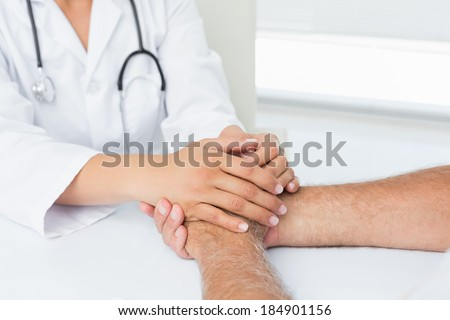 Close-up mid section of a doctor holding patients hands at medical office - stock photo