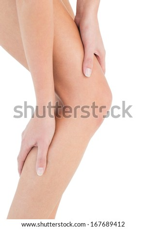 Close-up mid section of a fit young woman with leg pain over white background - stock photo
