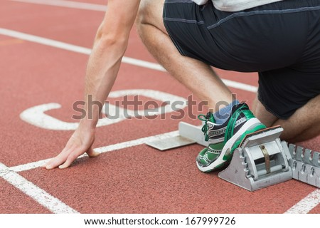 Close-up mid section of a young man ready to race on running track - stock photo
