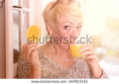 Close up Middle Age Blond Woman Drinking Orange Juice and Holding an Orange Fruit Slice While Leaning on the Wall and Looking at the Camera. - stock photo