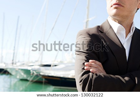 Close up middle section of a businessman standing by a luxurious yachts marine with his arms crossed against a deep blue sky and sea. - stock photo