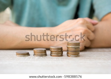 Close up money coins stack in saving money and growing with people background, concept save money finance
