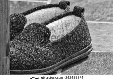 Close-up monochrome view of men's fuzzy slippers on a slate floor..