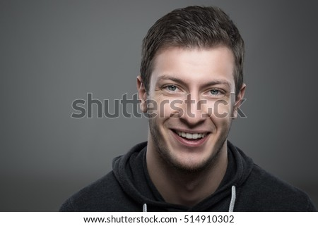 Close up moody portrait of young unshaven man smiling and looking at camera over gray background with copyspace