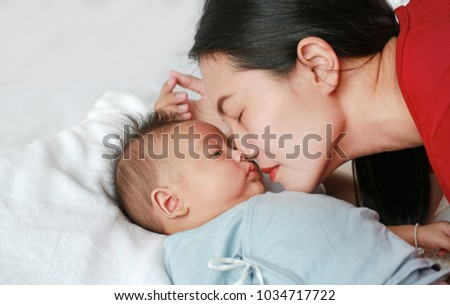 Close up mother kissing baby boy lying on the bed.