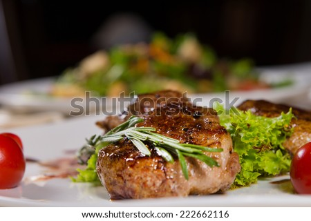 Close up Mouth Watering Tender Juicy Grilled Meaty Main Dish with Vegetables on White Plate Dine on the Table. - stock photo