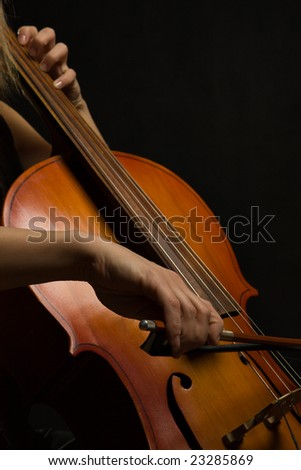 Close up musician hands with cello on a dark background - stock photo