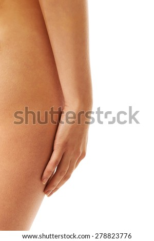 Close up naked woman touching her thigh.