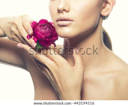 Close-up natural lips and open shoulders of caucasian brunette young woman posing with peony flower in hands. Studio portrait. Isolated on white background. Toned - stock photo
